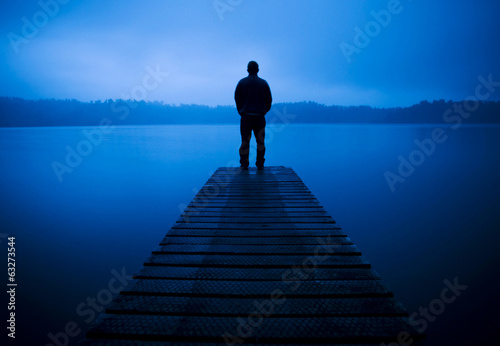 Obraz Man Standing on a Jetty by Tranquil Lake - fototapety do salonu