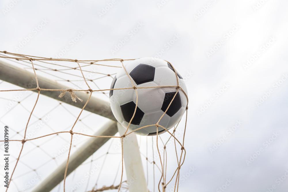 Soccer football in goal net