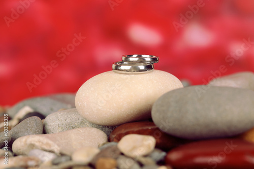 Wedding rings on rocks on red background