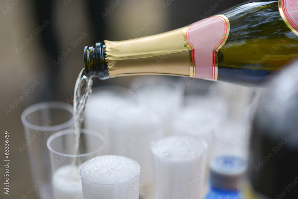 Fotografija  Someone poured a bottle champagne in glasses