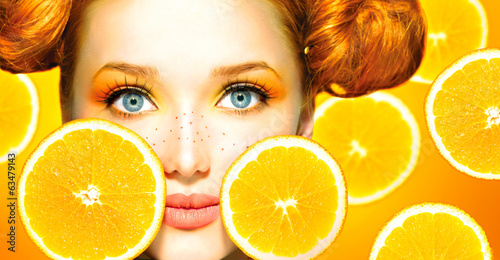 Beauty model girl with juicy oranges. Freckles