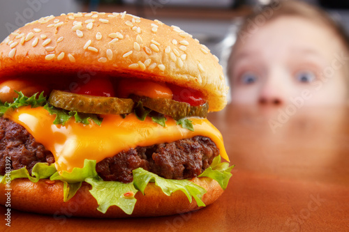 Fototapeta Hungry young boy is staring and smelling a burger obraz