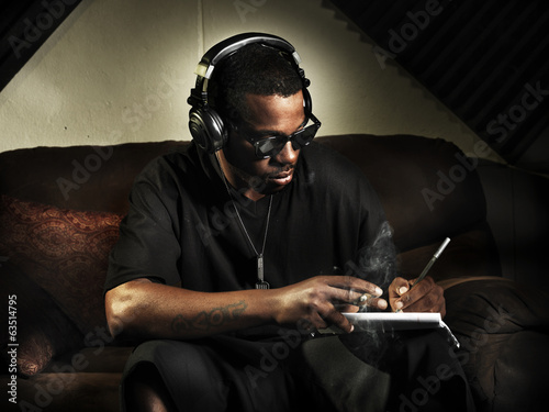 dj writing lyrics on note book in studio Poster