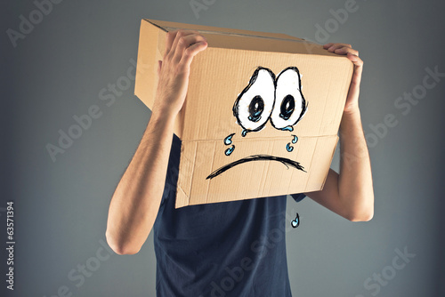 Photo Man with cardboard box on his head and sad face expression
