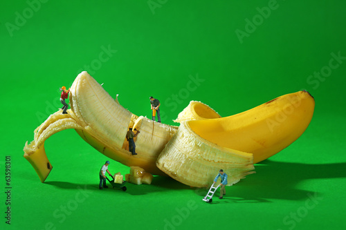 Fotografie, Obraz  Construction Workers in Conceptual Food Imagery With Banana