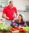 senior man in red and woman cooking together