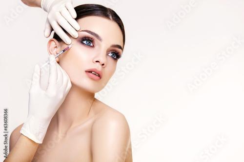 Photo  Beautiful woman gets injections. Cosmetology. Beauty Face
