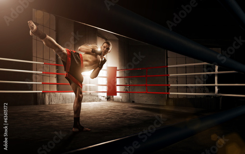Young  man kickboxing in the Arena Wallpaper Mural