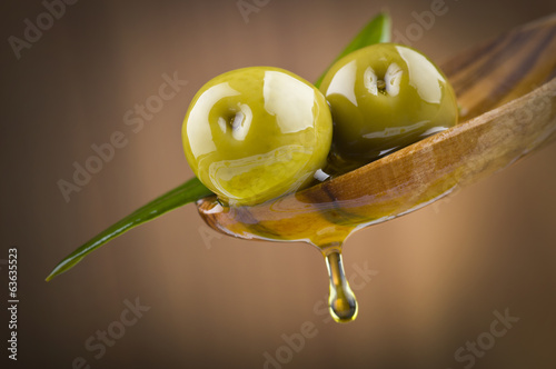 Fotobehang Planten Two olives and leaves with drop oil on wood spoon