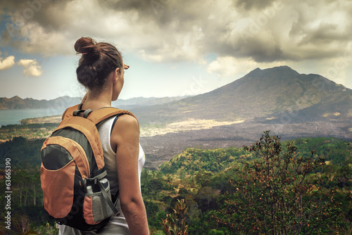 Fototapeta Lady tourist with a backpack standing on top of the mountain obraz