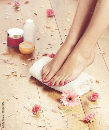 Poster Pedicure Spa background with beautiful legs, flowers and petals