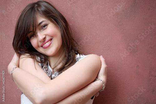 Ragazza sorridente appoggiata al muro