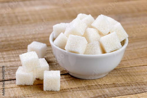 Fotografie, Obraz  Sugar cubes in bowl on wooden table