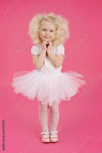Fotografie, Obraz  Little girl in a tutu skirt on pink background