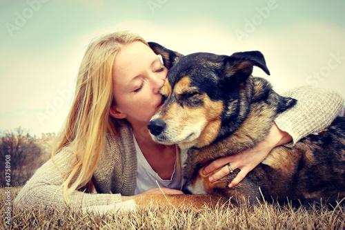 Fotografía  Woman Tenderly Hugging and Kissing Pet Dog