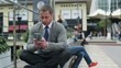 Businessman sitting on street bench and finish texting on cellph