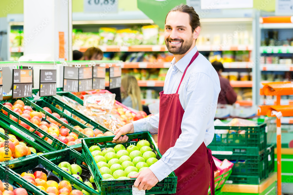 Fototapeta Supermarkt Angestellter füllt Regale auf