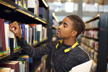 Young Man Looking For Books At...