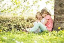 Zwei Mädchen Sitzten Unter Einem Baum