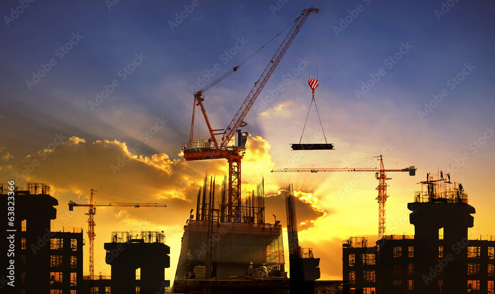 Fototapeta big crane and building construction against beautiful dusky sky