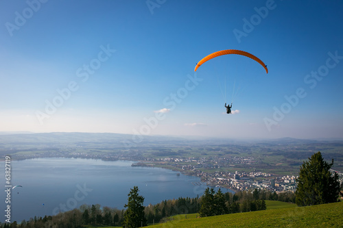 Foto op Canvas Luchtsport Paraglider over the Zug city, Zugersee and Swiss Alps during a s