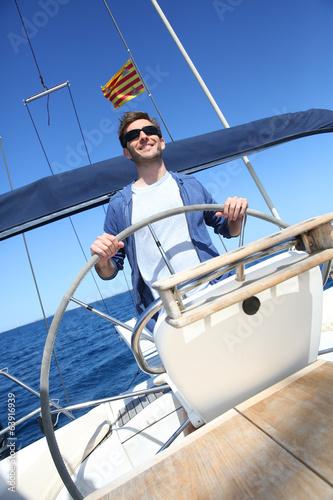 Fotografía  Skipper on sailboat navigating in mediterranean sea