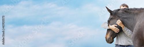 Foto op Canvas Paarden Man hugging his black horse's head against sky, banner