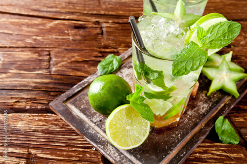 Fresh mojito drinks on wooden background