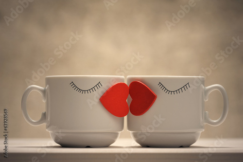 Two coffee cups with red hearts as a kissing lips