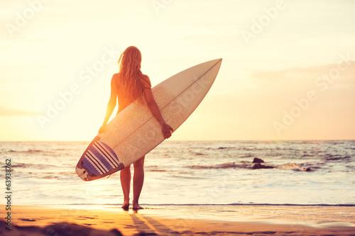 Plakat Surfingowiec dziewczyna na plaży przy zmierzchem