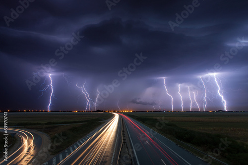 Foto auf Leinwand Onweer Thunderstorm and lightnings in night over a highway with car lig