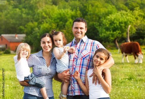 Fototapeta Young family with three children on the farm obraz