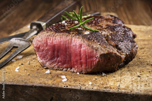 Fotobehang Steakhouse Steak auf altem Schneidebrett