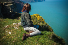 Young Woman Sitting On Edge Of...