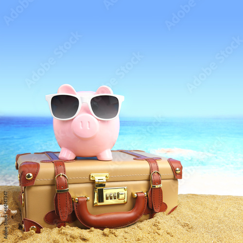 Cuadros en Lienzo  Maleta con la hucha en gafas de sol en la playa tropical