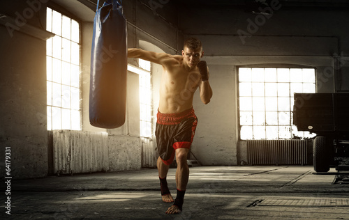 Fotografie, Tablou Young man boxing workout in an old building