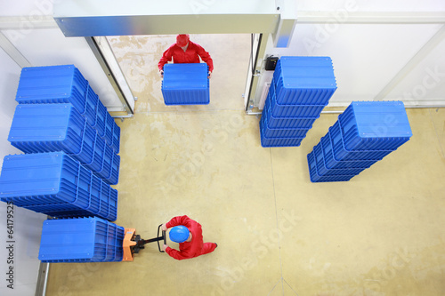 Fotografie, Obraz  two workers working with plastic blue boxes in small warehouse