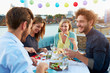 canvas print picture - Group Of Friends Eating Meal On Rooftop Terrace