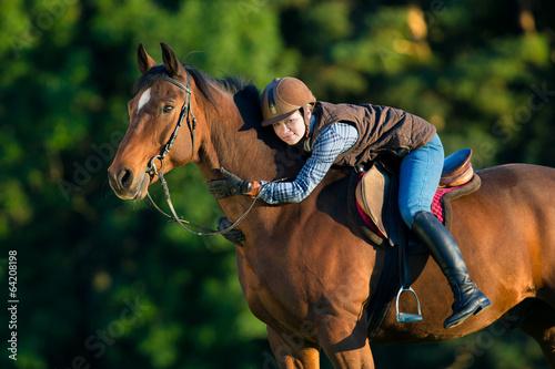 Fotografie, Tablou  Young woman riding a horse, horse riding back.