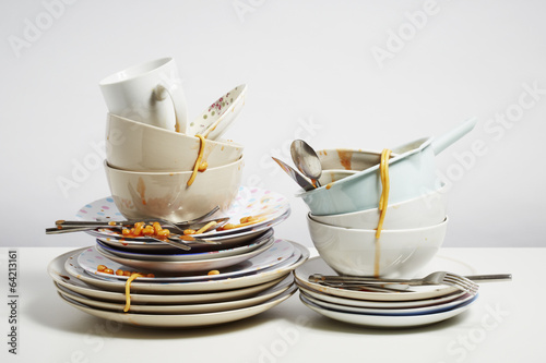 Fotografía  Dirty dishes pile needing washing up on white background