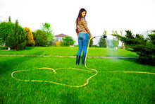 Smiling Woman Is Watering Gras...