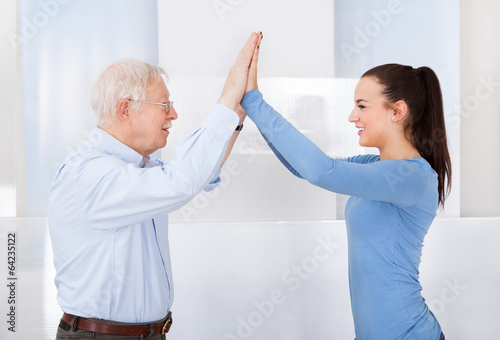 Fotografie, Obraz  Caregiver And Senior Man Giving High Five