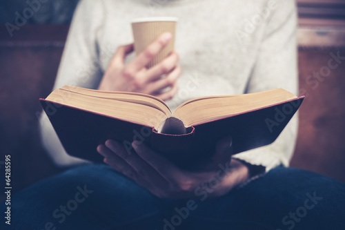 Fotografie, Obraz  Man reading and drinking from paper cup