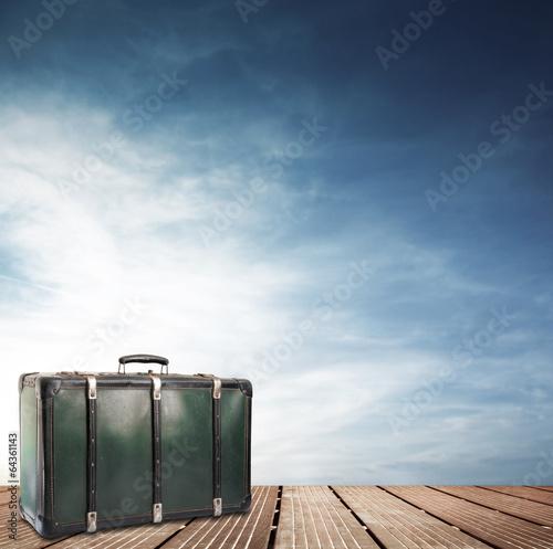 Fotografija vecchia valigia su passerella di legno