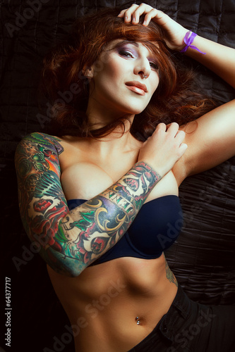 Beautiful girl with stylish make-up and tattooed arms: