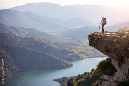 Obraz Female hiker standing on cliff and enjoying valley view - fototapety do salonu