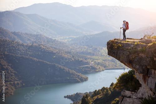 Fototapeta Female hiker standing on cliff and enjoying valley view obraz