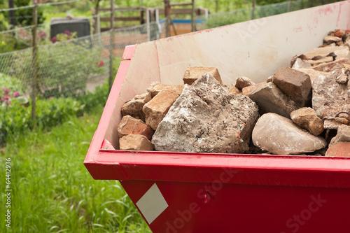 Fotografía  Ein roter Container gefüllt mit Bauschutt