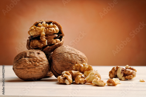 Fotografía  group of walnuts on a table with brown background