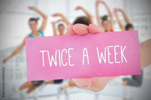 Woman holding pink card saying twice a week